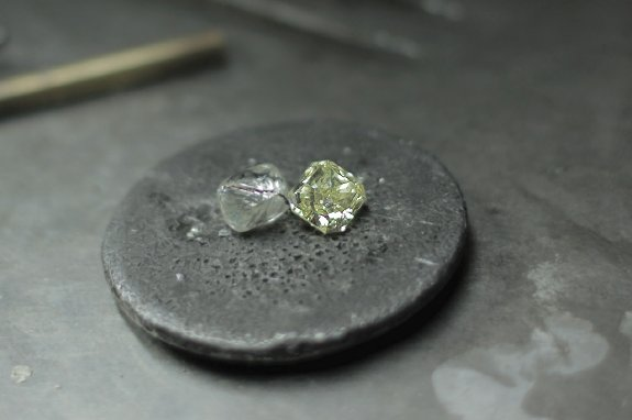 A rough diamond next to a polished diamond