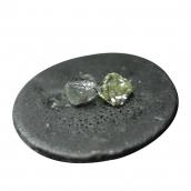 A polished diamond next to a rough diamond