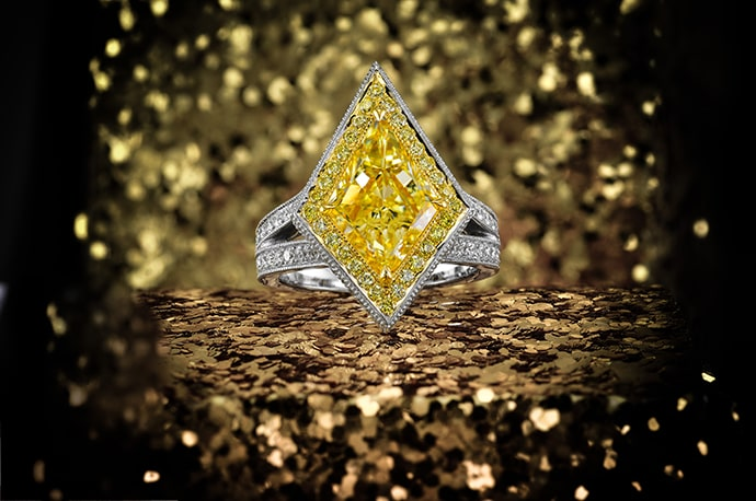 A 3.97 carat yellow diamond kite, halo ring