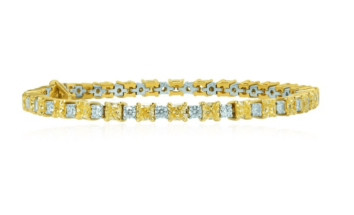 A stunning 8.37 ct TW Fancy Yellow radiant and collection white diamond bracelet mounted in 18K white and yellow gold.
