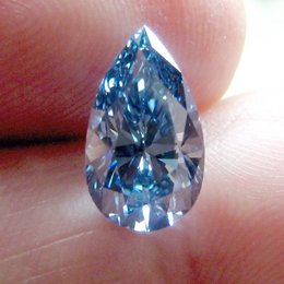 3+ Carat Fancy Vivid Blue Pear Held in Hand