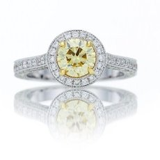 1.01 Carat, Fancy Yellow round mounted in a full pave halo ring with a delicate millgrain edge