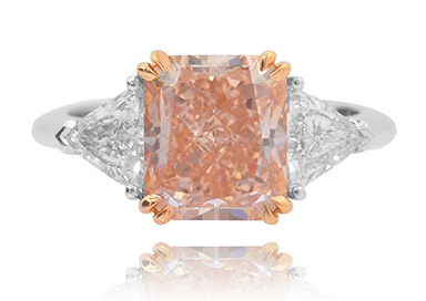 A 4.82 carat Leibish & Co. Fancy Orangy Pink and trilliant collection color 3 stone diamond ring